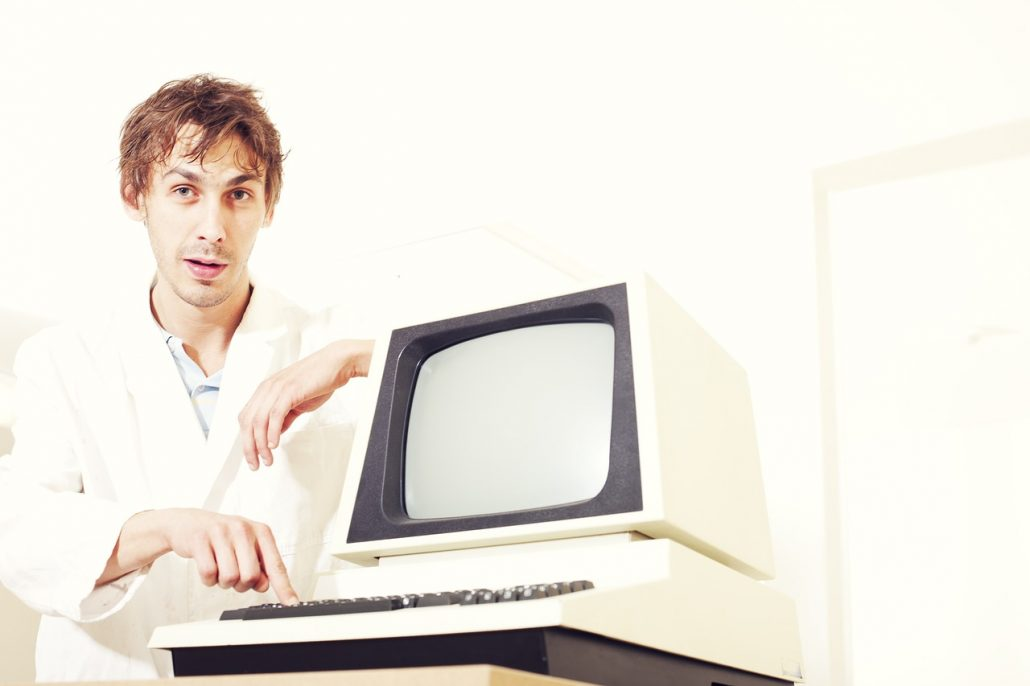 A clueless person in a lab coat typing on an old computer